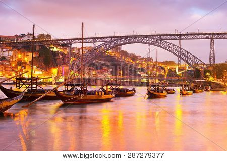 Scenic Sunset Over Douro River With Traditional Wine Boats, Illuminated Porto Skyline And Dom Luis I