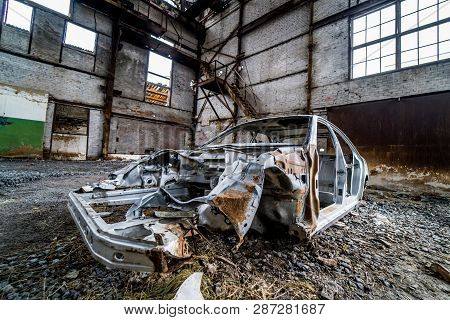 Abandoned In The Empty Building The Old Rusty Cab Of The Passenger Car. The Frame Of Damaged Car On