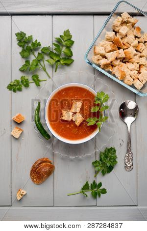 Tomatoes Soup With Croutons On A Grey Wooden Board