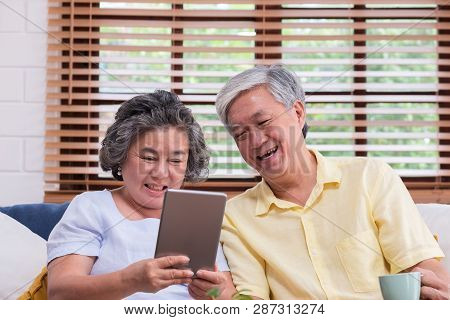 Asian Senior Couple Learn To Using Table Compute On Sofa In Living Room At Home.senior With Technolo