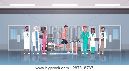Doctors Group Checking Male Patient Running On Treadmill With Electrodes Attached To Body Sports Car