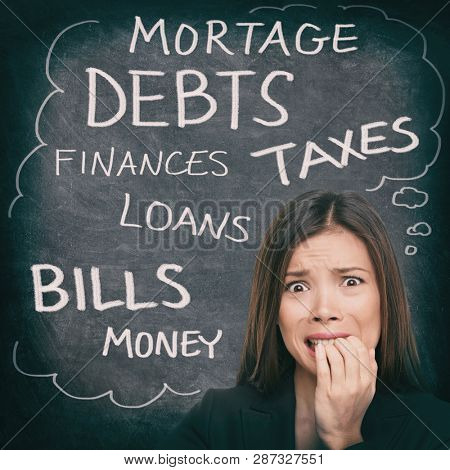 Financial stress Asian woman stressed with money problems bad credit, loans, debts, mortgage payments. Bills to pay worried person on black chalkboard with finance words written.