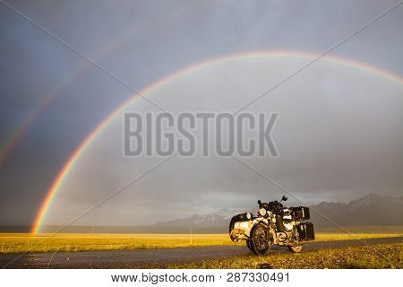 A Sidecar Motorcycle Backed By A Mountain Range, Under A Rainbow.