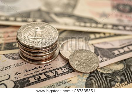 A Stack Of Coins On Dollar Bills
