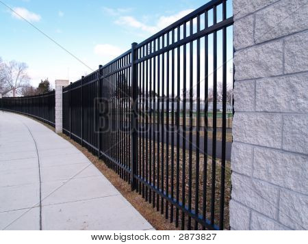 Tall Curving Black Fence By A Sidewalk
