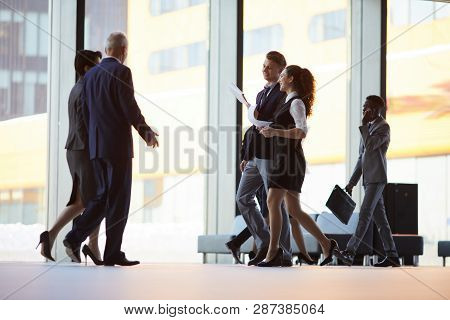 Group Of Business People Walking Across Office Hall Of Lobby, Copy Space