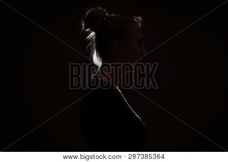 Profle View Of Woman Hiding In The Dark To Preserve Anonymity - Backlit Contour With Rim Light