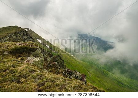 Landscape With Clouds Covering Mountain Peaks. Hiking In Nature On The Top Of The Mountain. Hiking I