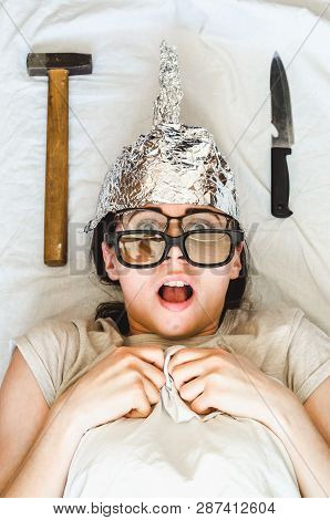 Insane paranoid woman wears foil hat and sleeps with weapon and different glasses because of phobias. Concept of schizophrenia, mental illness and anxiety poster