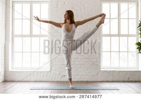 Young Woman Practicing Yoga, Standing In Utthita Hasta Padangustasana
