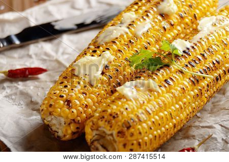 Kitchen Table With Grilled Sweet Corn Cob Under Melting Butter And Greens On Baking Paper