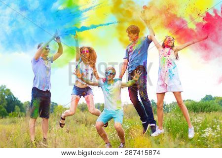 Cheerful And Happy Friends Soiled By Bright Paints Jumping And Laugh In Colorful Smoke On Nature. Co