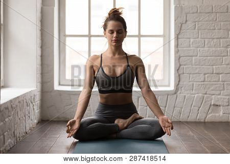 Calm Woman Practicing Yoga, Sitting In Padmasana Pose, Lotus Exercise