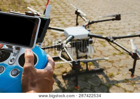 Man Controlling Agriculture Drone. Remote Controller