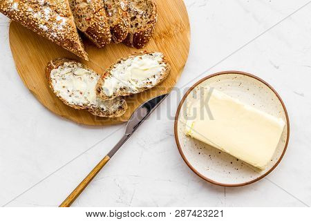 Slice Of Bread With Butter On White Background Top View
