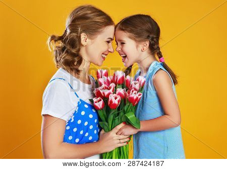 Happy Mother's Day! Child Daughter   Gives Mother A Bouquet Of Flowers On Color Yellow Background.