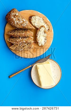 Wholegrain Bread On Cutting Board With Butter On Plate, Slice Of Bread With Butter On Blue Backgroun