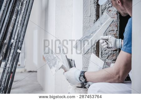 Caucasian Masonry Worker With Brick And Finishing Trowels In His Hands. Construction Industry Theme.