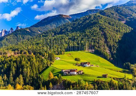 Delightful mountain valley in the Dolomites. Picturesque farms with red roofs are built on the slopes of the mountains. The concept of ecological and photo tourism