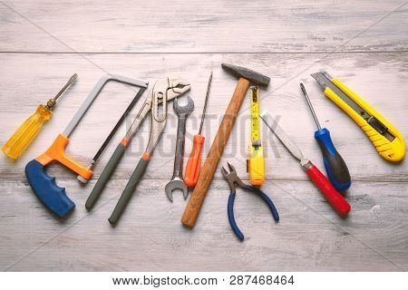 Screwdriver,hammer,tape Measure And Other Tool For Construction Tools On Gray Wooden Background With