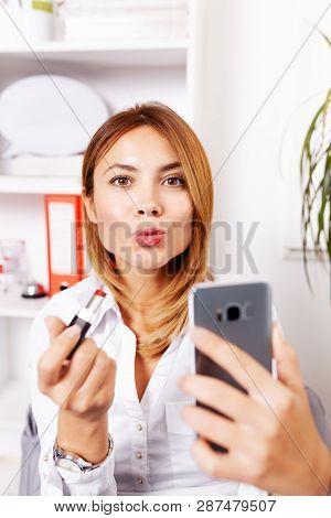 Business Woman Putting On Lipstick