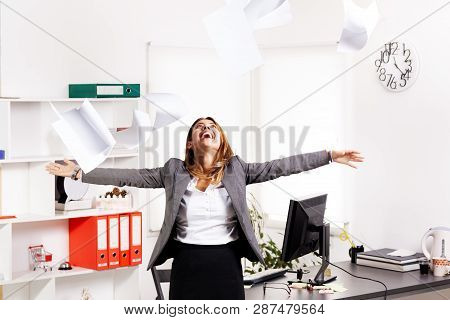 Business Woman In Office Throwing Papers In The Air