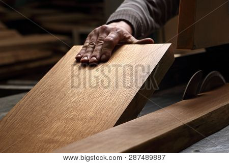 Joinery. The man saws boards. A carpenter cuts a plank on a circular saw. poster