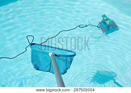Pool Skimmer And Underwater Cleaning Robot In Swimming Pool. Cleaning Pool Concept