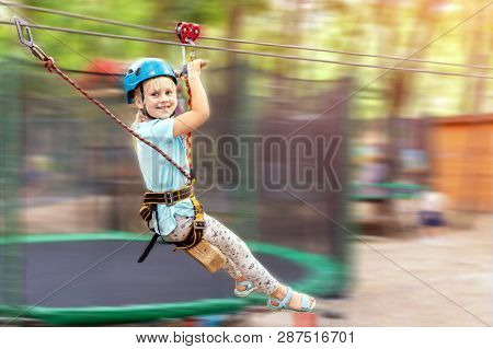 Cute Little Funny Caucasion Blond Girl In Helmet Having Fun Riding Rope Zipline In Adventure Park. C