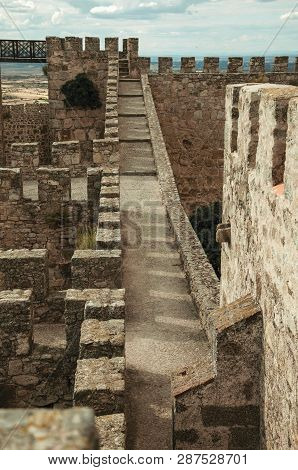 Pathway On Top Of Thick Stone Wall With Crenel And Merlons At The Castle Of Trujillo. A Small Mediev