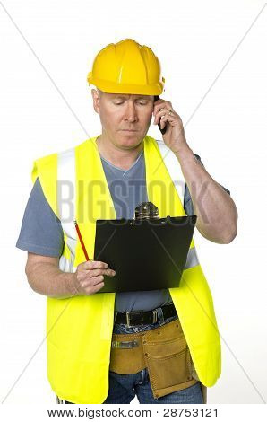 Construction Worker Phones And Looks At Clipboard