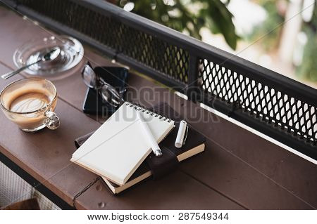 Abstract Scene Of Coffee Cup, Notebooks,and Mobile Phone On Rustic Wood Counter. Coffee Break And Re