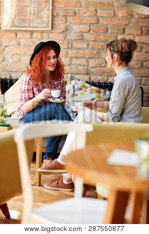 Female friends talking and drinking cappuccino in pub