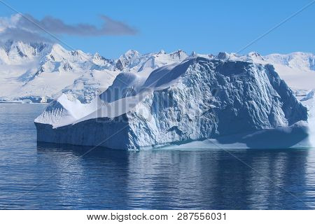 Iceberg And Mountains In Antarctica. A Large Iceberg Floating Along The Coast Of The Antarctic Penin