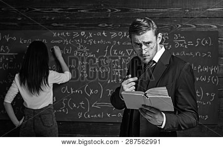 Strict Teacher In Glasses Giving Explanations While Holding Book. Tutor Helping His Young Female Stu