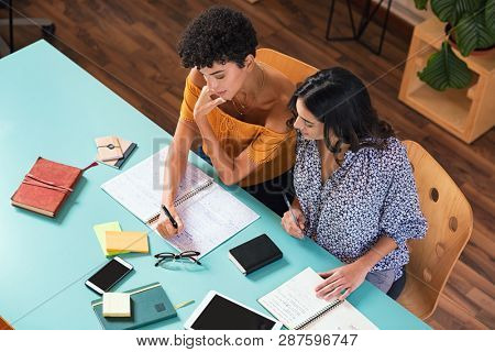 Two young women studying in library together, preparing for exams. High angle view of brazilian student discussing her studies with a girl friend. Top view of two college students studying.