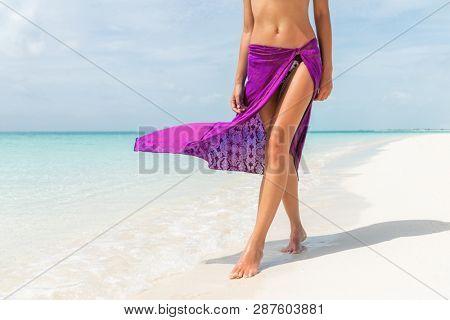 Beach legs bikini body woman walking on caribbean holiday destination with pink skirt fashion beachwear sun tanning relaxing in sun.
