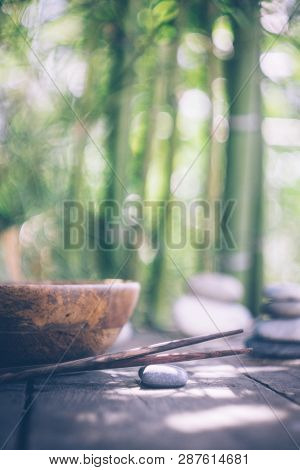 Detox Food Concept: An Empty Wooden Bowl, Wooden Chopsticks, Bamboo, Stones On An Old Wooden Table.