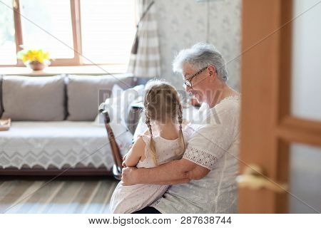 Grandmother Is Hugging Granddaughter In Cozy Home Living Room. Kind Senior Woman Is Telling Story Or