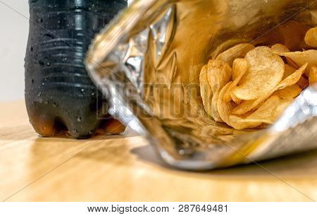 Opened Bag Of Potato Chips With A Bottle Of Soft Drink In The Background