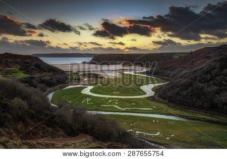 Sunset At Three Cliffs Bay Evening Sky Over The River At Three Cliffs Bay And The Great Tor At Penma