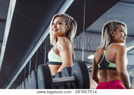 Fitness Woman Lifting Weight In The Gym Stands Next To Dumbbells