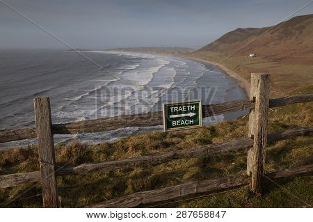 Editorial Swansea, Uk - February 17, 2019: A Bilingual Welsh And English Signpost To The Beach At Rh