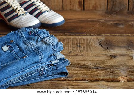Teenager Casual Outfit. Boys Shoes, Clothing And Accessories On Wooden Background -  Jeans, Sneakers