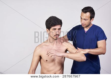 Doctor Examining His Patient Arm In A Clinic