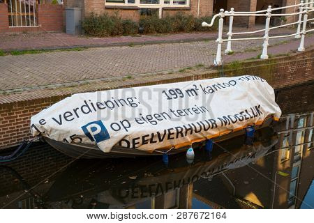 Leiden, Holland - February 25, 2019: Funny Dutch text on the boat tarp, for rent 199 square meters on the first floor