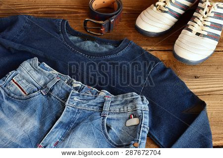 Teenager Casual Outfit. Boys Shoes, Clothing And Accessories On Wooden Background - Sweater, Trouser