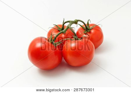Ripe Tomatoes Isolated On White Background. Four Whole Vegetables With Sepals And Branch