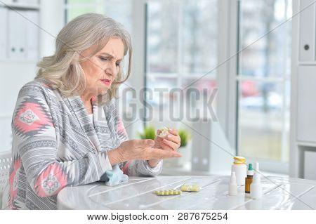 Portrait Of Sick Senior Woman Sitting At Table Wit Medicine