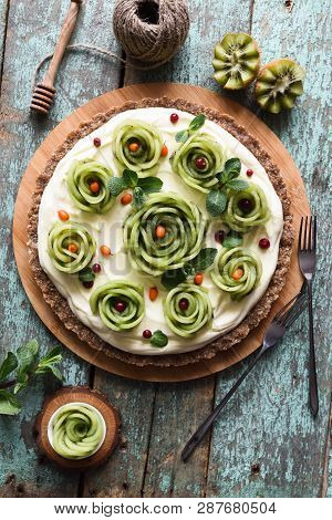 Raw Vegetarian Healthy Dessert. Homemade Pie With Kiwi Roses, Berries, Mint And Cream Filling On Nut